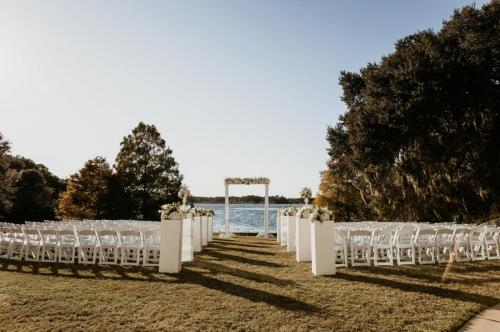 White folding chairs set up for wedding facing West Crystal Lake with arch at alter