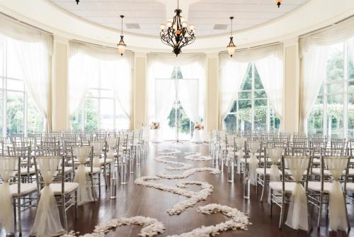 Silver chiavari chairs set up in Rotunda for wedding ceremony with flower petal design down aisle.