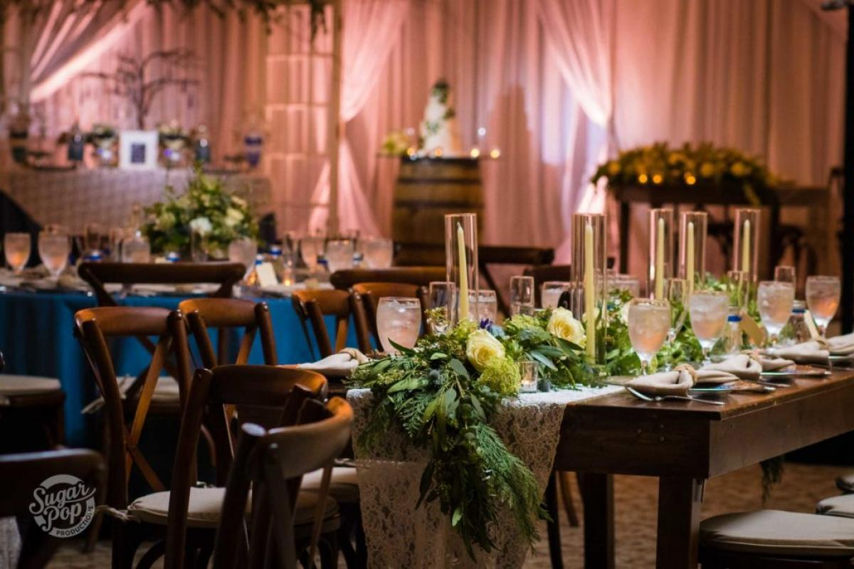 Farm style tables with candles and floral in Grand ballroom