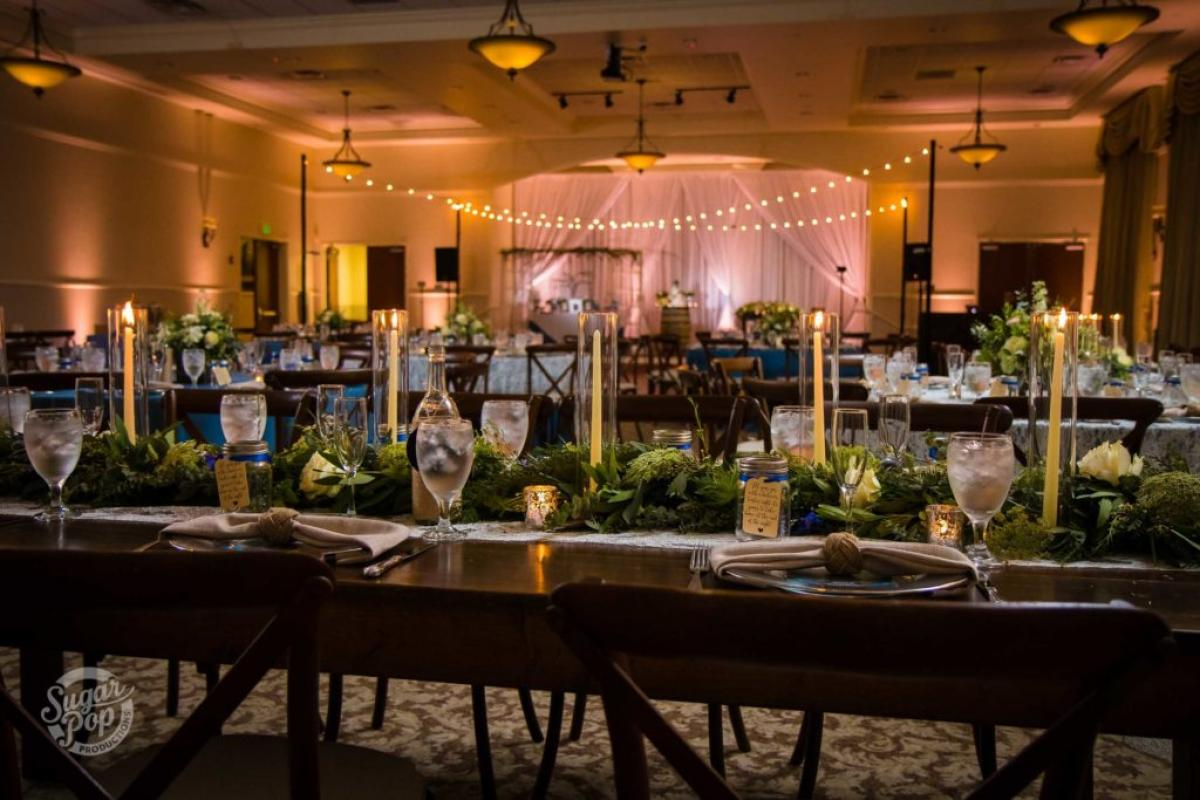Farm style table with greenery and candles and market lighting over dance floor