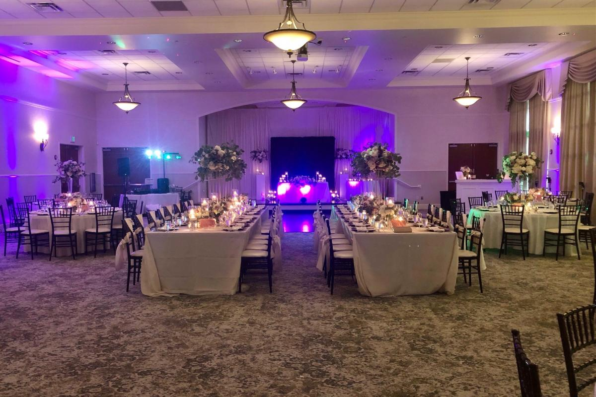 Grand ballroom reception with uplighting and candles on tables