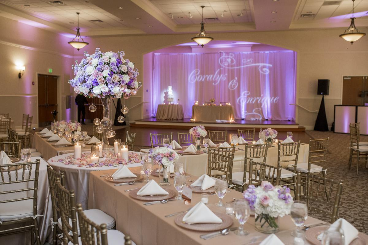 Reception in grand ballroom with tables set with linens and floral arrangements