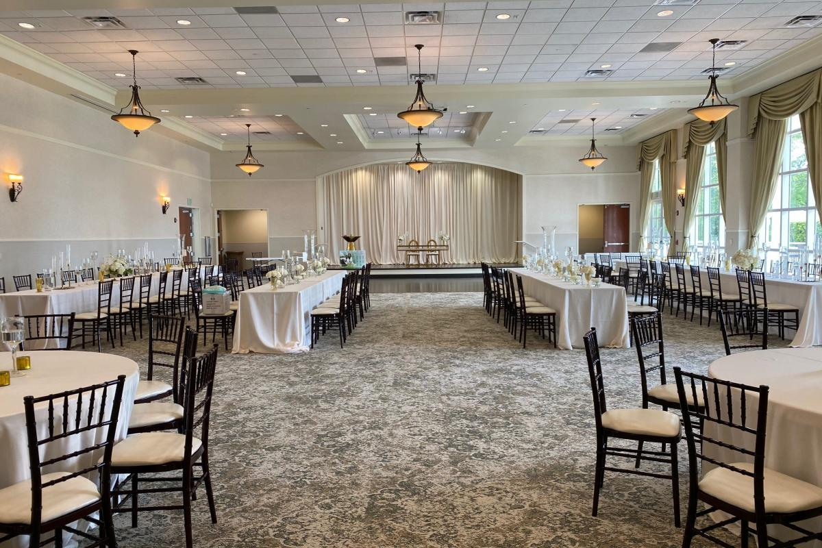 Grand ballroom set for reception with draping on stage and tables set