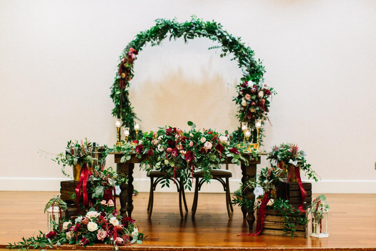 Sweetheart table with altar behind. All covered in greenery and floral.