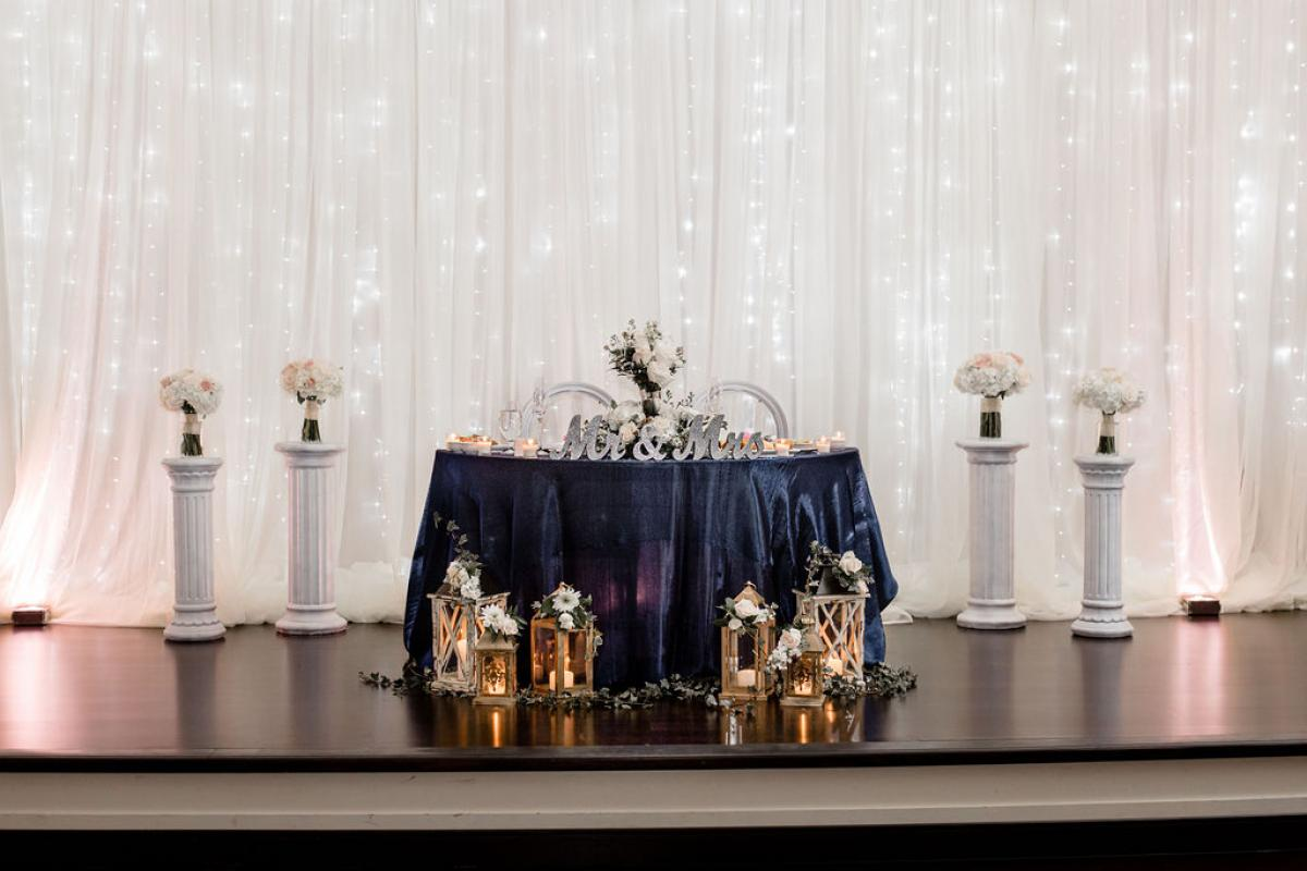 Sweetheart table on stage with lanterns and flowers on pillars