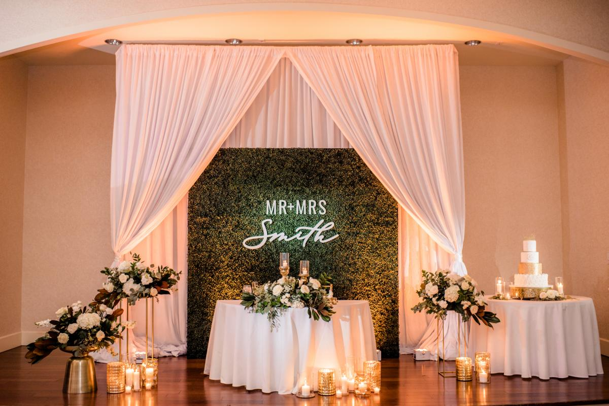 Grand Ballroom stage with draping and boxwood hedge backdrop