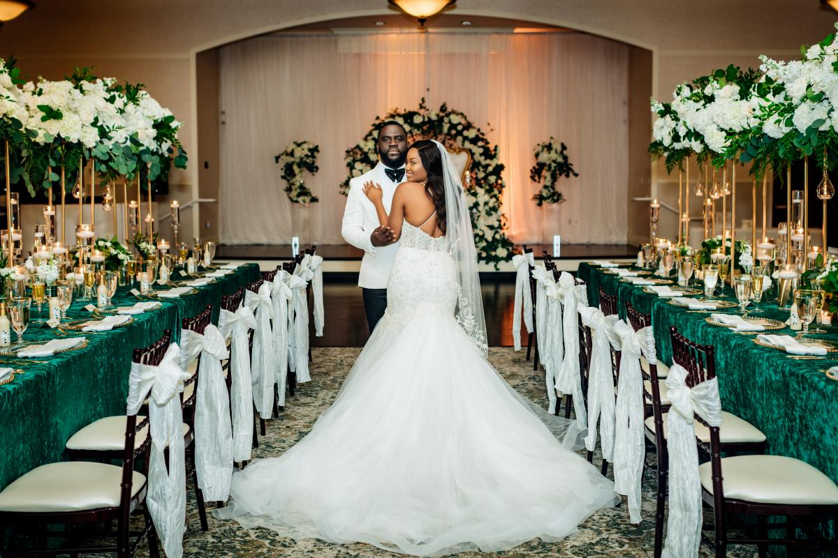 Couple posing for photo in Grand Ballroom with reception tables set