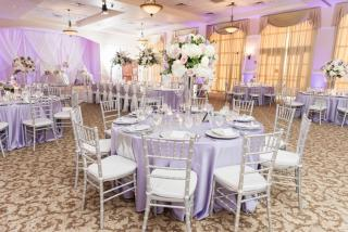 Grand Ballroom set up for reception with linens, silver chiavari chairs, draping on stage, and floral centerpieces